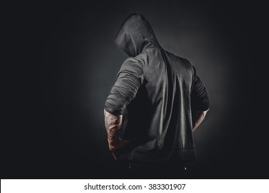 Back view of muscular male bodybuilder posing in studio over black background