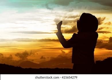 Back view of muslim woman praying wearing hijab
