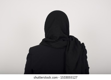 The back view of a muslim woman wearing hijab standing against gray wall. Studio Shoot.