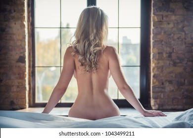 Back view of naked blonde woman looking out the window while sitting on bed