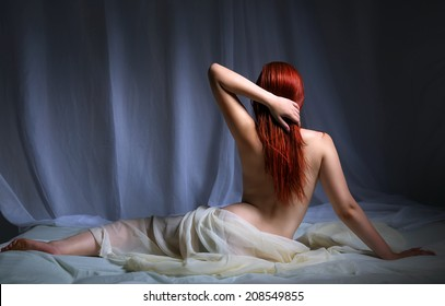 Back view of a naked redhead woman sitting on the bed