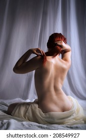 Back view of a naked woman covered with sheets sitting on the bed