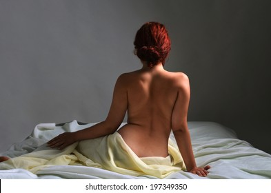 Back view of a naked woman sitting on the bed cover with sheets