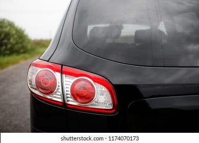 Back view of new black car. Closeup headlights of car. Black premium city crossover, luxury SUV rear light closeup. Car lamp close-up.