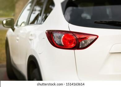 Back view of new white car. Closeup headlights of car. White premium city crossover, luxury SUV rear light closeup. Car lamp close-up.