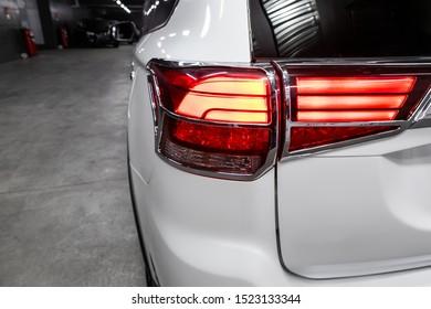 Back view of new white city crossover. Closeup headlights of car  SUV. Modern rear light closeup. Car lamp close-up.
