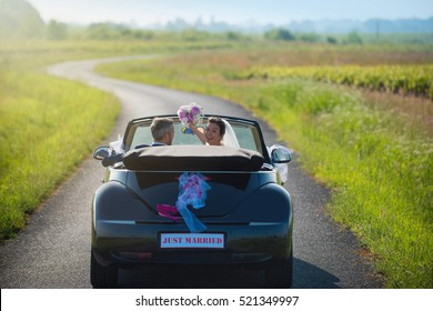 back view ,newlyweds who go on honeymoon by car on a country road. the bride holds her bouquet  in air, she is smiling at camera. The shape of the car has been modified so as not to be recognizable