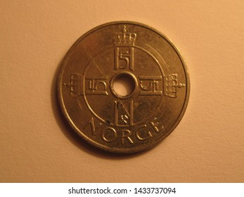 Back view of Norwegian coin. 1 krone from Norway. Great for numismatic collection. Shiny coin from Norway isolated on yellow surface of paper.