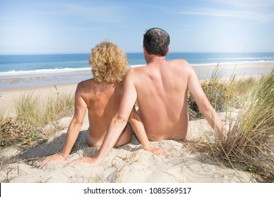 back view of nude nudist couple in sea sand vacation