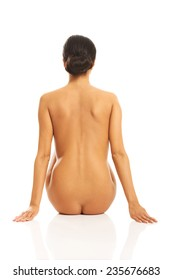 Back view of nude woman sitting supports the floor.