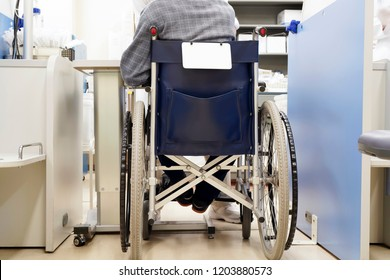 Back view of old man sitting on wheelchair, consultation in a medical room,