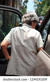 Back view of old women driver.  Closeup elderly open door and going in the car. Background with blurry street. Concept Ability of old people, elderly day, take care of old people, Holiday and Travel