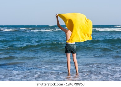 Back view on the boy standing on seashore of the beach in the yellow towel  and looking on the sea. Concept.