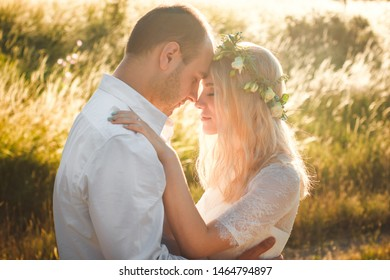 Back view on bride and groom holding hands in sunny summer day. Outdoor wedding and relationsheep romantic concept