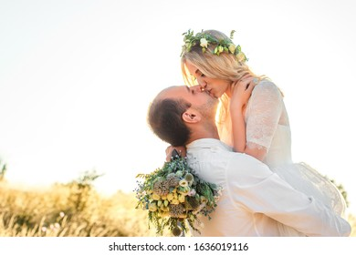 Back view on bride and groom holding hands in sunny summer day. Outdoor wedding and relationsheep romantic concept. Selective soft focus.