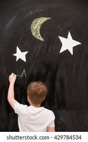 Back view on cute kid boy drawing stars with chalk on a black board with white stars and moon. Child writing on wall in the classroom. Creativity, activities for children indoors. Dreaming about space