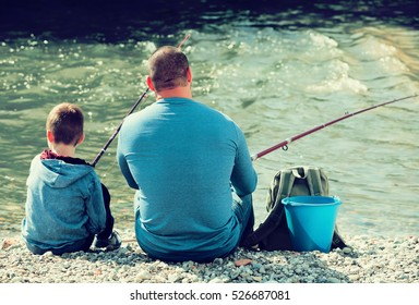 Back view on father and teenager son fishing together in wild river