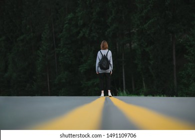 Back view on a female hiker walking down the asphalt road in the woodland. Tourist woman with a backpack standing in the middle of the highway near the fir forest. Travel concept.