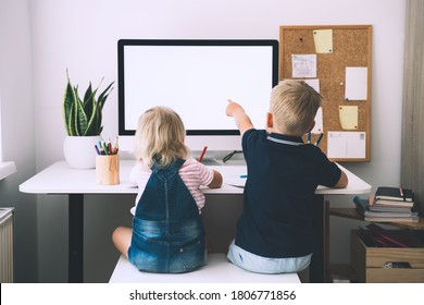 Back view on little preschool boy and girl sitting at working desk with computer with blank white screen at home. Kids and computer technologies. Children online learning, development or entertainment