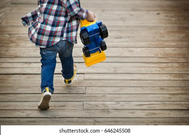 Back view on little toddler boy with his toy tractor in his hands running on wooden bridge outdoors. Child rushing away. Lifestyle