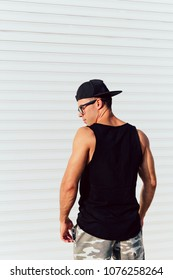 Back view on strong muscular young man standing against the white wall, wearing black singlet, shorts and cap. Outdoors.