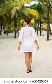 Back view on woman on tropical vacation at caribbean resort beach. Brunette model wearing summer fashion sunglasses and white kaftan. Riviera Maya, Mexico.