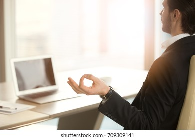 Back view over shoulder of calm businessman meditating in yoga pose in front of laptop in modern office setting. Reducing discomfort at workplace, staying in focus, relieving stress at work concept.