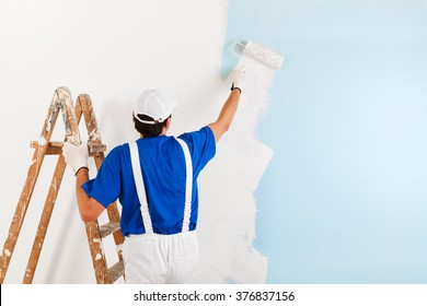 Back view of  painter with cap and gloves painting a wall with paint roller and wooden vintage ladder, with copy space