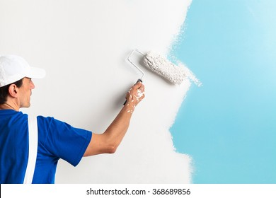 Back view of painter painting a wall with paint roller, with copy space