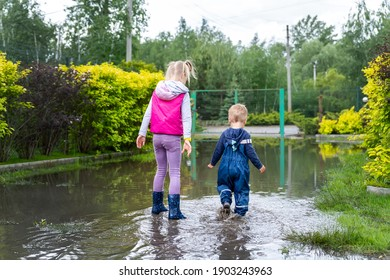 Back view of pair of two cute blond caucasian little children brother and sister enjoy have fun playing jumping in dirty puddle wearing blue waterproof pants and rubber rainboots at street outdoors