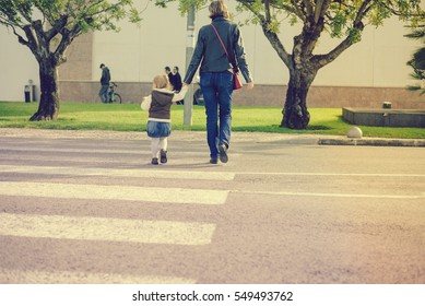 Back view of parent with child walking on sunny road outdoors background. Childcare, love and safety lifestyle