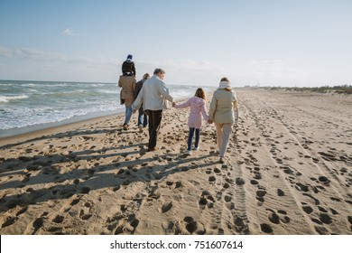 back view of parents piggybacking son while grandparents holding hands with granddaughter, walking together at seaside