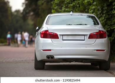 Back view part of white car parked on city pedestrian zone pavement on background of blurred silhouettes of people walking along green sunny summer alley. Modern city lifestyle concept.