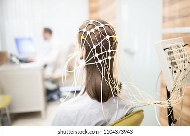Back view of patient with eeg equipment on her head during brain activity clinical test