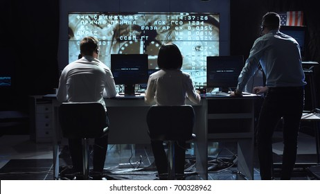 Back view of people working and managing flight in mission control center. Docking to the international space station in space. Elements of this image furnished by NASA.
