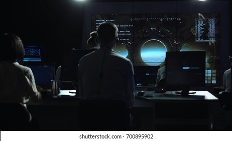 Back view of people working and managing flight in mission control center. The spacecraft lands on the moon. Elements of this image furnished by NASA.