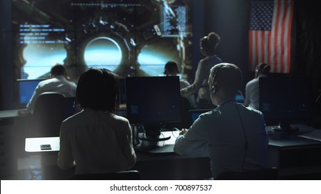 Back view of people working and managing flight in mission control center.