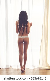 Back view of a perfect female body. Woman in sexy white lingerie is standing near the window, full length