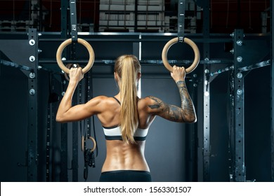 Back view of perfect fit young caucasian woman with ponytail in sports wear. Healthy young woman exercising with gymnastic rings. Female bodybuilder with power hand, triceps, arms, rear in gym.