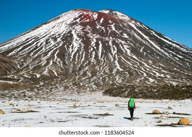 Back view of the person- traveler hiking and tramping with backpack in New Zealand's mountains, walking toward huge volcano Mount Ngauruhoe, Tongariro crossing in New Zealand's North Island