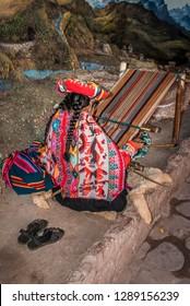 Back view of Peruvian woman weaving a striped textile