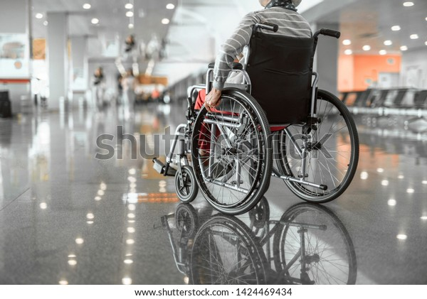 Back view photo of old woman moving in wheelchair in the lobby at airport. Copy space in left side