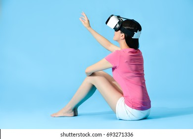 back view photo of pretty elegant woman using hand touching simulation screen when she sitting on blue background floor using VR goggles playing 3D game.