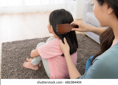 back view photo of young woman using brush combing little girl hair.