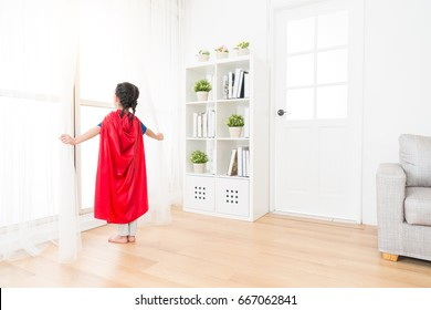 back view photo of youth lovely little girl children playing as superhero and standing on living room wooden floor opening curtain looking at window.