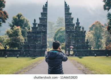 Back view of photographer take a photos of traditional Hindu gate in Bali island, Indonesia.