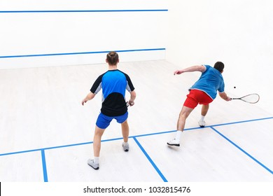 back view of players hitting a ball in a court. Men playing match of squash