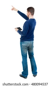 Back view of pointing business man. bearded man in blue pullover is holding tablet and shows a finger at the sky.