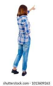 Back view of  pointing woman. beautiful girl. Rear view people collection.  backside view of person.  A girl in a blue shirt shows a sideways finger.
