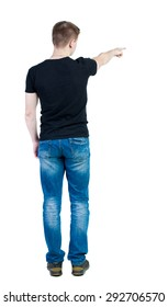 Back view pointing young men in shirt and jeans. Young guy gesture. Rear view people collection.  Isolated over white background. guy in black t-shirt stands and points his finger to right.
